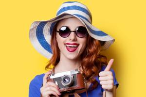 Smiling redhead girl in blue dress and hat  with camera on yellow background.